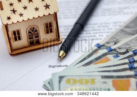 Model Of The House Near The Money And The Document On The Purchase Of Housing. Handle For Signing A