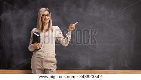 Young female teacher with books pointing to a blackboard