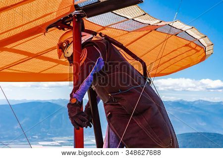 Man Preparing To Fly In A Hang Gliding. The Professional Pilot Of Hang-glider Getting Ready To Fly F