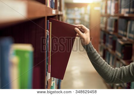 Asia Female Hand  Picking Book From Bookshelf At Library University,a Concept Of Learning And Choice
