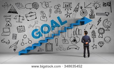 Businessman stands in front of a wall with stairs and the inscription Goal as strategy and goal concept (3d rendering)
