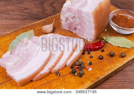 Partly Sliced Boiled-smoked Pork Belly On Rind With Layers Of Lean Meat Among The Some Spices On The