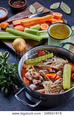 Cooked Chicken Stock With Vegetables And Aromatic Herbs In A Stockpot And In A Mug At The Background