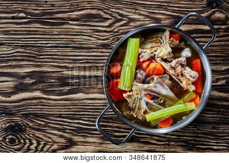 Cooked Chicken Stock With Vegetables And Aromatic Herbs In A Stockpot On A Rustic Wooden Kitchen Wor