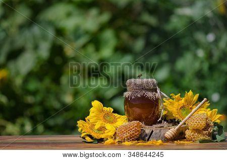 Bee Sitting On Glass Of Honey. Honey With Flying Honey Bee