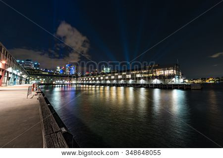 Beautiful Urban Night Scene With Water And Wharfs Illuminated At Night. Walsh Bay And Wharfs In Sydn