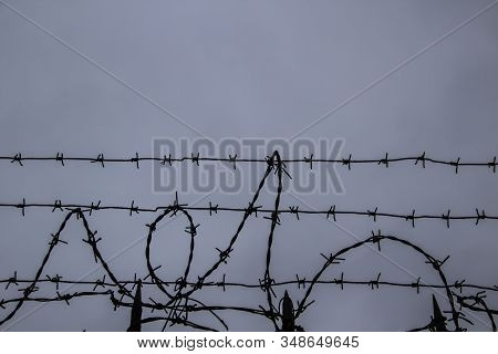 Barbed Wire Fence On Against Grey Sky Background.