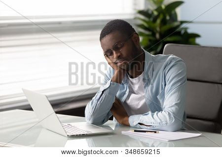 African Employee Falls Asleep Seated On Chair At Workplace