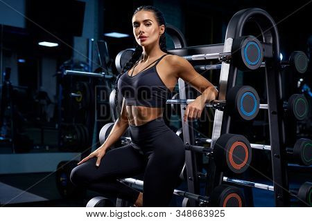 Side Close Up Of Female Bodybuilder With Long Braids Posing Near Stand With Sports Equipment. Srtong
