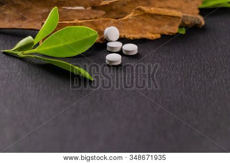Traditional Medicine Concept. Cinnamon And Ayurvedic White Tablets With Green Leaves On The Black Ba