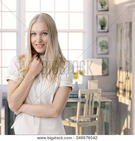 Attractive casual young blue eyed caucasian blonde woman standing at retro home. Smiling, looking at camera.
