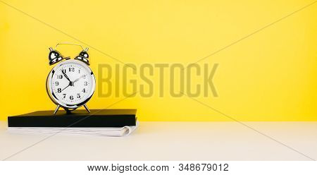 White New Metallic Mechanical Alarm Clock, Notebook, Sketchbook On White Table And Colorful Yellow B