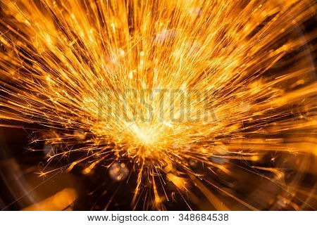 Sparks  Fire Closeup On A Black Background. Material Joining Production Process. Man Working On Iron
