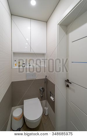 Modern Design Toilet With Beige And Brown Wall And Floor Tiles, Wooden Doors, White Built-in Toilet