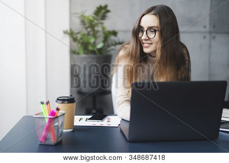 Young Professional Doing Creative Project On Laptop. Girl Sitting By Computer At Office Desk. Digita