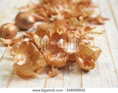 The Use Of Onion Peel In Medicine And For Coloring Easter Eggs. Onion Skin And Onion On A Wooden Whi