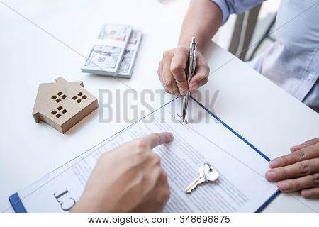Real Estate Agent Are Presenting Home Loan And Giving House, Keys To Customer After Signing Contract
