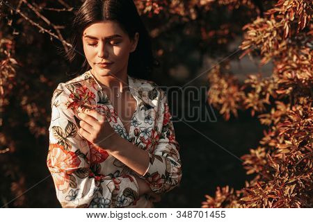 Calm Young Lady With Closed Eyes Admiring Small Flower And Resting Near Bushes In Spring Evening In