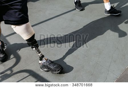 Modern Leg Prosthesis. Disabled Young Man With Foot Prosthesis Walks Along The Street.