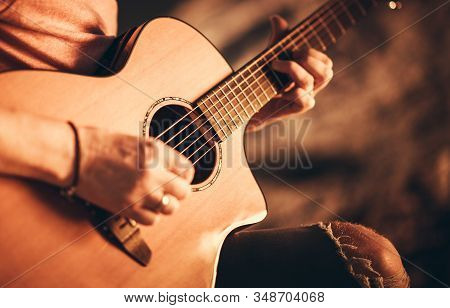Caucasian Singer Musician With Classic Acoustic Guitar. Guitar Ballad Playing Closeup Photo.