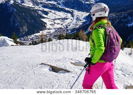 Girl Skier Looking Down Towards Corvara Mountain Village In The Italian Dolomites, From A Ski Slope
