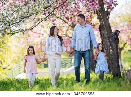 Young Parents With Small Daugthers Walking Outside In Spring Nature.