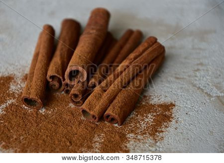 Cinnamon Sticks And Cinnamon Powder On A Stone Background. Close-up. Side View. Natural Light