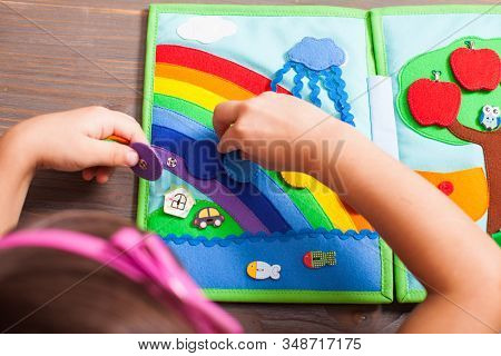 The Preschool Girl Learns Colors With The Help Of Developing Book