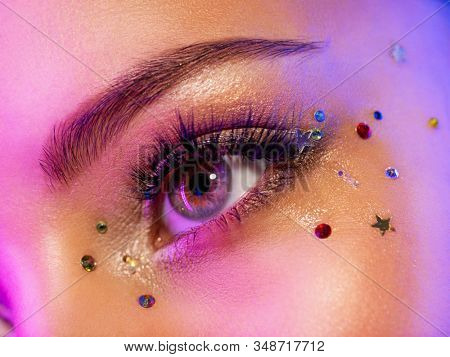 Colorful makeup. Bright and intense makeup. Female eye close-up with bright makeup. Fashionable stylish makeup with the use of sequins. Stylish image. The face is illuminated by bright lights.