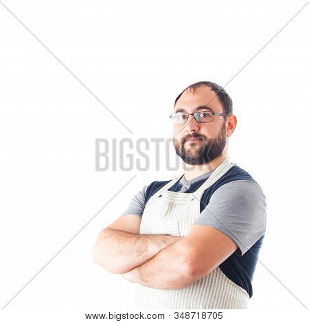 Confident Young Handsome Man In Apron Keeping Arms Crossed And Standing Against White Background