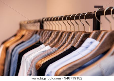 Closeup Colorful Male, Female Clothes In Boutique Hanging On Hangers, Clothing Rack On Metal Stand.