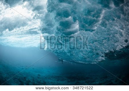 Underwater view of the surfer passing the ocean wave