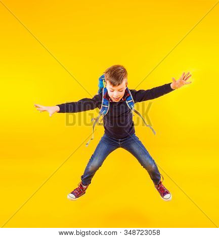 Happy Kid Jump With Hand Up. Cute Exciting Child Boy Ready To Study With Backpack Isolated On Yellow