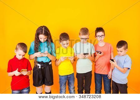 Young Kids Playing Game On Mobile Phone
