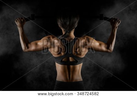 Muscular woman doing pull up exercise on horizontal bar. Back training