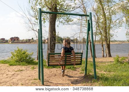 Young Woman Swinging On A Swing. Girl Sitting On A Swing