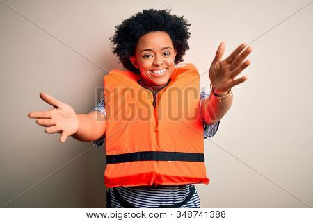 Young African American afro woman with curly hair wearing orange protection lifejacket looking at the camera smiling with open arms for hug. Cheerful expression embracing happiness.
