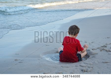 A Little Boy In A Puddle On The Beach. The Child Sits In A Wet Puddle. The Child On The Sand. The Bo