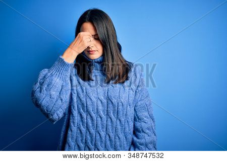 Young brunette woman with blue eyes wearing casual turtleneck sweater tired rubbing nose and eyes feeling fatigue and headache. Stress and frustration concept.