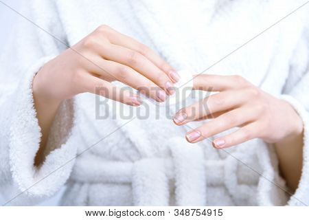 Closeup Female Hands Are Holding White Cotton Cosmetic Sponge. Young Woman Is  Erasing Polish From N