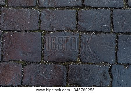 Black Stones Of An Old Pavement. Backdrop Background Texture, Square Rectangular Geometric Cobblesto