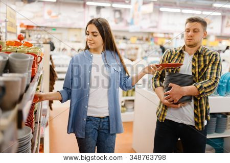 Young couple choosing plates in houseware store