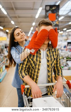 Young playful couple, shopping in houseware store