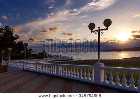 Gelendzhik Embankment At Sunset. In The Foreground Is A Balustrade That Extends Into The Distance, A