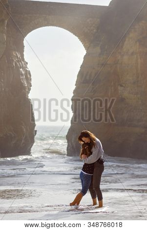 Loving Mother Embraces Little Daughter Standing Barefoot In Atlantic Ocean, Tourists Enjoy Picturesq