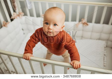 Beautiful Little Girl In A Crib In A Cozy Light Room In A Sweater Of Fashionable Shades. Learns To S