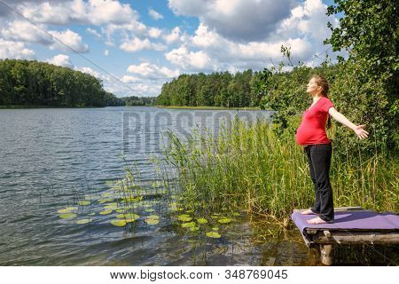 Young pregnant woman sanding on a wooden pier at a forest lake during warm sunny day spreading out her hands enjoying nature - healthy pregnancy lifestyle concept