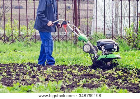 A Man Cultivates The Land With A Cultivator In A Spring Garden.