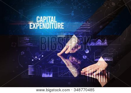 Businessman touching huge screen with CAPITAL EXPENDITURE inscription, cyber business concept