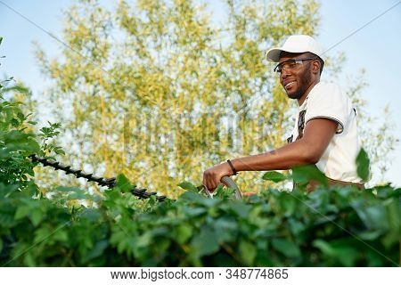 African Male Gardener Wearing Overalls With Protective Glasses Working With Professional Garden Equi